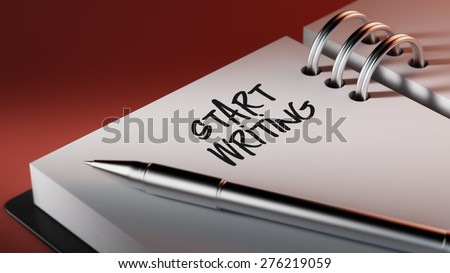 Closeup of a personal agenda setting an important date writing with pen. The words Start Writing written on a white notebook to remind you an important appointment.