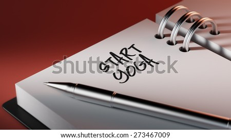 Closeup of a personal agenda setting an important date writing with pen. The words Start Yoga written on a white notebook to remind you an important appointment.