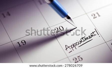 Closeup of a personal agenda setting an important date written with pen. The words Appointment written on a white notebook to remind you an important appointment.