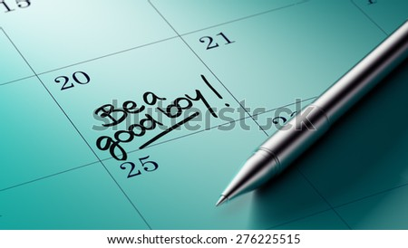 Closeup of a personal agenda setting an important date written with pen. The words Be a good boy written on a white notebook to remind you an important appointment.
