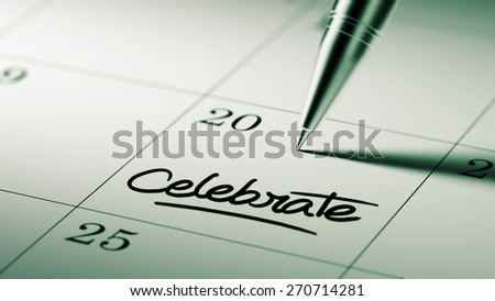 Closeup of a personal agenda setting an important date written with pen. The words Celebrate written on a white notebook to remind you an important appointment.