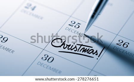 Closeup of a personal agenda setting an important date written with pen. The words Christmas written on a white notebook to remind you an important appointment.