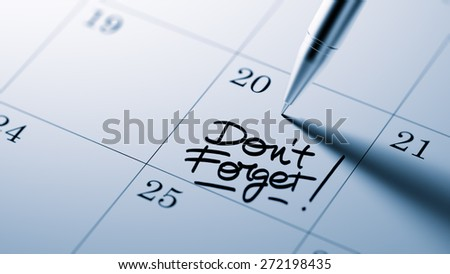 Closeup of a personal agenda setting an important date written with pen. The words Don`t Forget written on a white notebook to remind you an important appointment. - stock photo