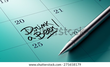 Closeup of a personal agenda setting an important date written with pen. The words Drink a beer written on a white notebook to remind you an important appointment.