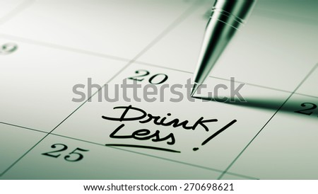 Closeup of a personal agenda setting an important date written with pen. The words Drink Less written on a white notebook to remind you an important appointment.