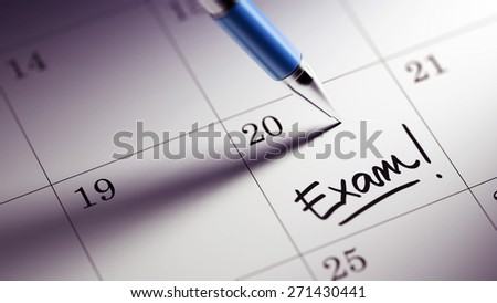 Closeup of a personal agenda setting an important date written with pen. The words Exam written on a white notebook to remind you an important appointment.