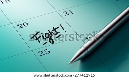 Closeup of a personal agenda setting an important date written with pen. The words Fight written on a white notebook to remind you an important appointment.