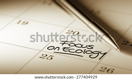 Closeup of a personal agenda setting an important date written with pen. The words Focus on Ecology written on a white notebook to remind you an important appointment.