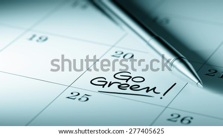 Closeup of a personal agenda setting an important date written with pen. The words Go Green written on a white notebook to remind you an important appointment. - stock photo