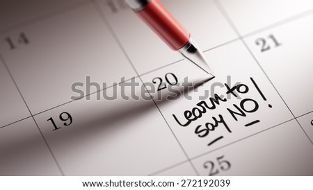 Closeup of a personal agenda setting an important date written with pen. The words Learn to say no written on a white notebook to remind you an important appointment. - stock photo