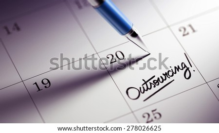 Closeup of a personal agenda setting an important date written with pen. The words Outsourcing written on a white notebook to remind you an important appointment.