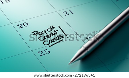 Closeup of a personal agenda setting an important date written with pen. The words Pay off Credit cards written on a white notebook to remind you an important appointment.