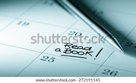 Closeup of a personal agenda setting an important date written with pen. The words Read a book written on a white notebook to remind you an important appointment. - stock photo