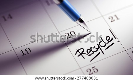 Closeup of a personal agenda setting an important date written with pen. The words Recycle written on a white notebook to remind you an important appointment.