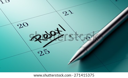 Closeup of a personal agenda setting an important date written with pen. The words Relax written on a white notebook to remind you an important appointment.