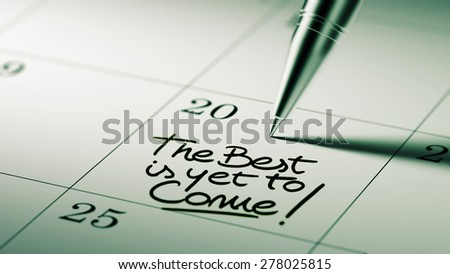 Closeup of a personal agenda setting an important date written with pen. The words The best is yet to come written on a white notebook to remind you an important appointment.