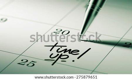 Closeup of a personal agenda setting an important date written with pen. The words Time up written on a white notebook to remind you an important appointment.