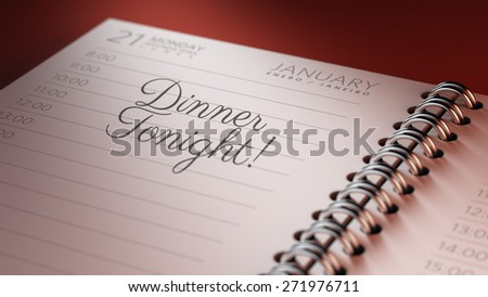 Closeup of a personal calendar setting an important date representing a time schedule. The words Dinner written on a white notebook to remind you an important appointment.
