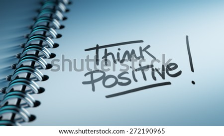 Closeup of a personal calendar setting an important date representing a time schedule. The words Think positive written on a white notebook to remind you an important appointment. - stock photo