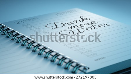 Closeup of a personal calendar setting an important date representing a time schedule. The words Drink more water written on a white notebook to remind you an important appointment. - stock photo