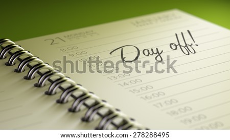 Closeup of a personal calendar setting an important date representing a time schedule. The words Day off written on a white notebook to remind you an important appointment.