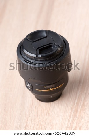 Closeup of a photographic lens on wooden table