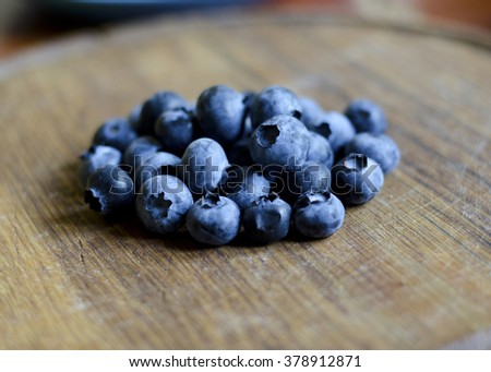 Closeup of a pile of blueberries against a worn wooden background (shallow DOF)