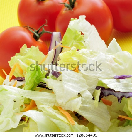closeup of a pile of chopped lettuce mix and some tomatoes, ready to make a salad