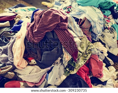 closeup of a pile of different used clothes on sale in a flea market, with a filter effect - stock photo