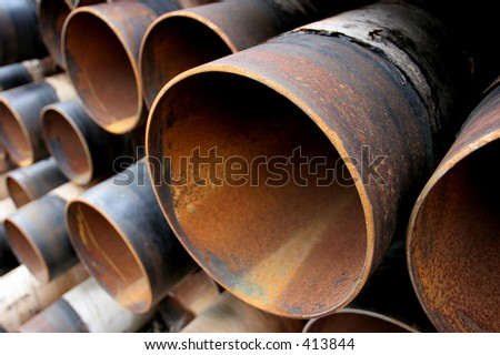 closeup of a pile of large and rusting steel pipes - stock photo