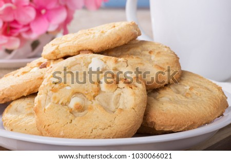 Closeup of a pile of macadamia nut cookies on a plate with coffee cup and flowers in background