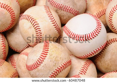 Closeup of a pile of old used baseballs with one new ball in the middle. Horizontal format.