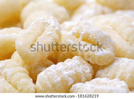 closeup of a pile of uncooked gnocchi on a white background  - stock photo
