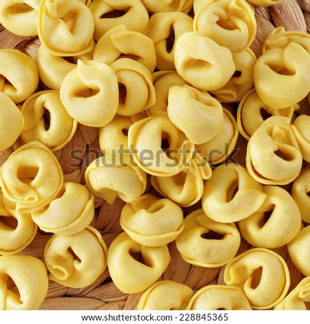 closeup of a pile of uncooked tortellini ready to be cooked - stock photo