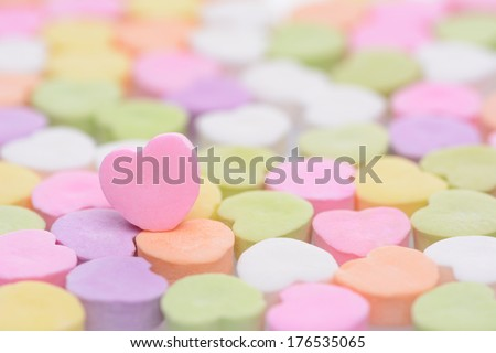 Closeup of a pink candy heart for Valentines Day standing out in a field of out of focus similar candies. Heart is set to one side leaving room for your copy. The candies are blank.  - stock photo