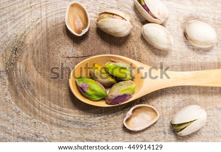 Closeup of a pistachios on wooden background.