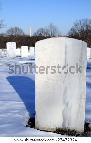 Closeup of a plain gravestone with copy space at the Arlington National Cemetery and the Washington Memorial in the background - stock photo