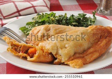 Closeup of a plate of chicken empanadas with kale salad - stock photo