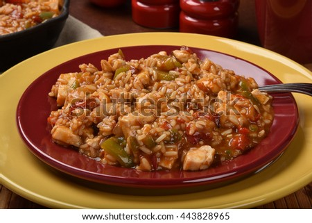 Closeup of a plate of chicken fajita rice with a cast iron serving skillet in the background - stock photo