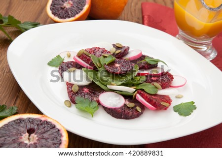 Closeup of a plate of juicy salad with blood oranges, radish, spinach, and pumpkin seeds. Citrus dressing.