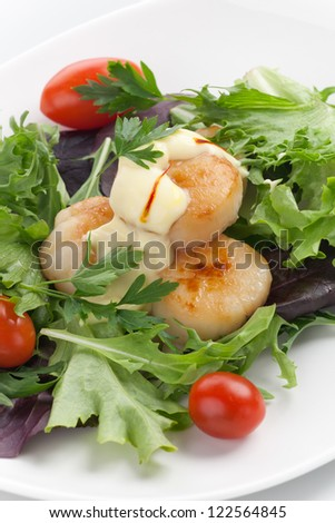 Closeup of a plate of scallops, cherry tomatoes and spring mix salad with Saffron dressing.