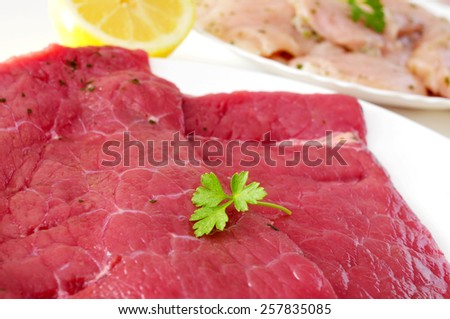closeup of a plate raw beef meat and a plate with raw turkey fillets in the background - stock photo
