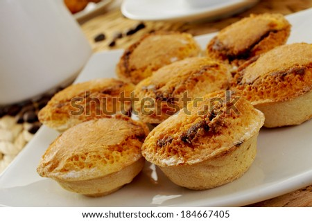 closeup of a plate with pasteis de feijao typical Portuguese pastries, on a set table - stock photo