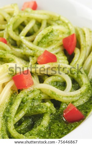 Closeup of a plate with spaghetti, green basil sauce and chopped red pepper - stock photo