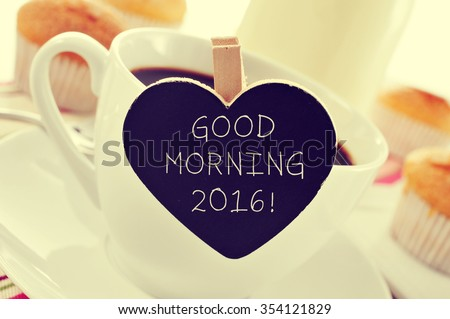 closeup of a porcelain cup of coffee with a heart-shaped signboard with the text good morning 2016 on a set table for breakfast - stock photo