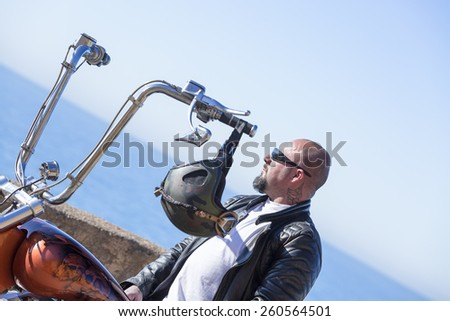 closeup of a portrait of a chopper motorcyclist sitting on his motorcycle enjoying the nice view at sunrise - focus on the face