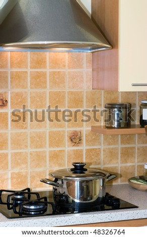 Closeup of a pot on the stove in the modern kitchen - stock photo