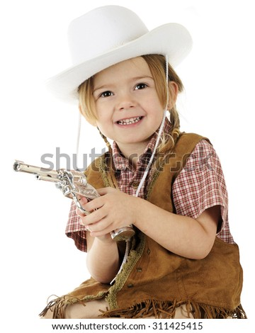 Closeup of a preschool cowgirl happily holding her gun.  On a white background. - stock photo