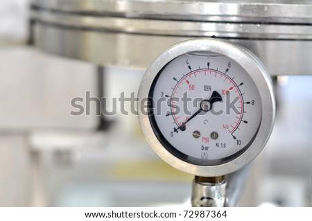 Closeup of a pressure meter on a machine - stock photo
