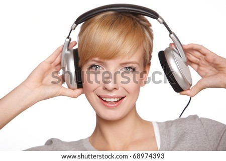 Closeup of a pretty blond female listening to music over headphones - stock photo